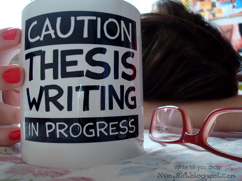 """Mug with """"Caution - Thesis Writing in Progress"""" written on it, person with head on desk, glasses"""