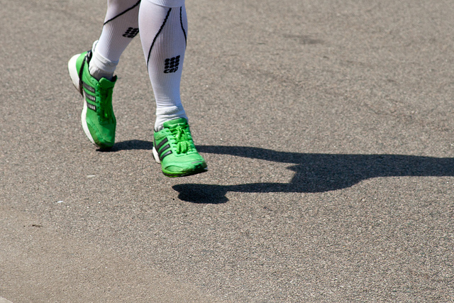 Legs running with green shoes on pavement