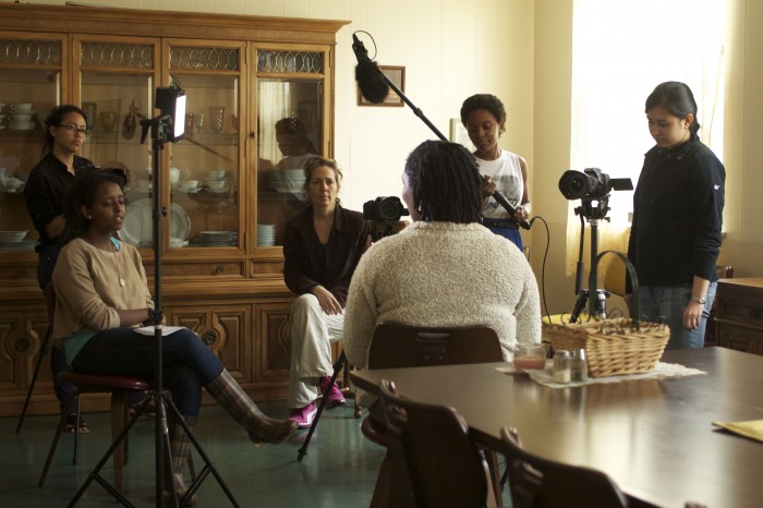 Four students operate a video camera, light, and microphone while talking with a seated woman