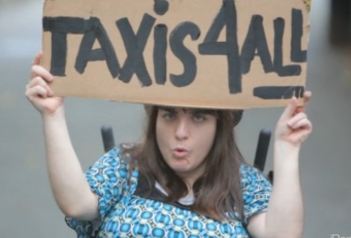 "Activist in wheelchair holds a sign saying ""Taxis 4 All"""