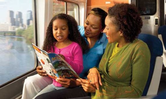 Image of two women with a girl, reading on the amtrak train.