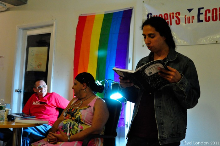 Person reading from a notebook, other people listening, rainbow flag in the background