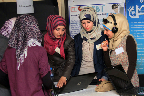 Four young women gathered around a laptop