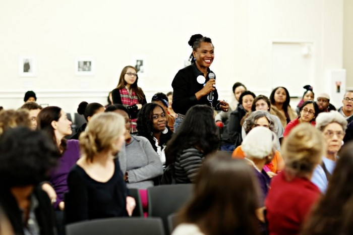 Women standing to ask a question, surrounded by audience