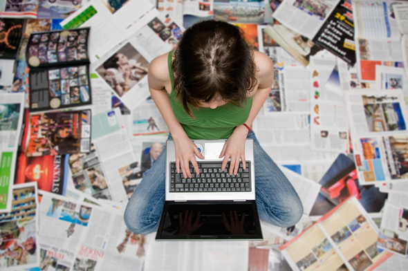 Young woman with laptop surrounded by magazines