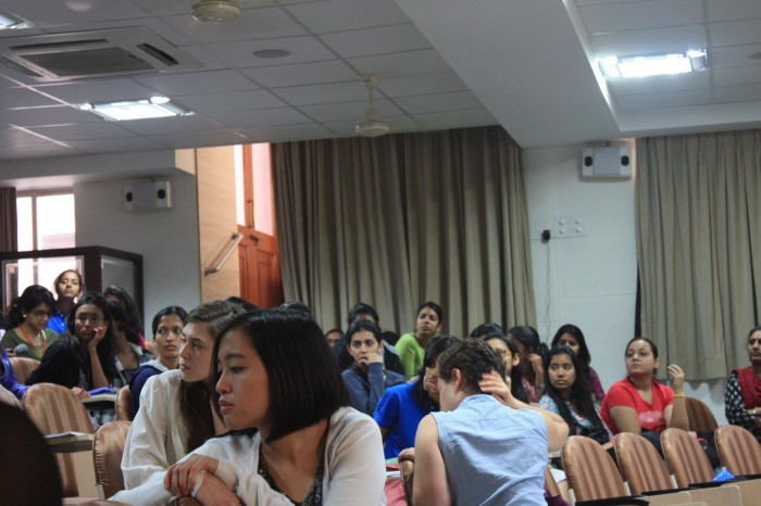 Group of students in auditorium style classroom, listening turned towards someone in the audience