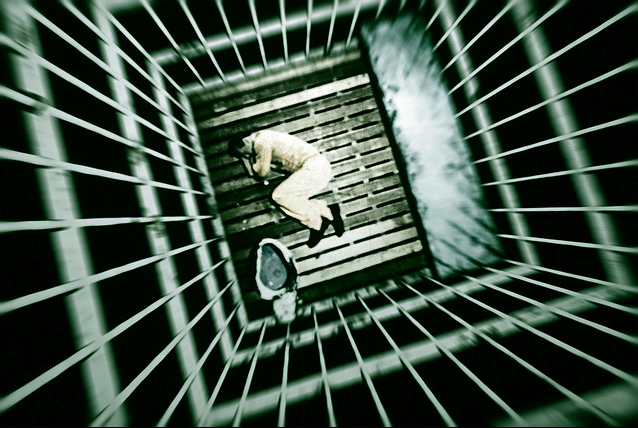 Incarcerated person lying on the floor of a small cell