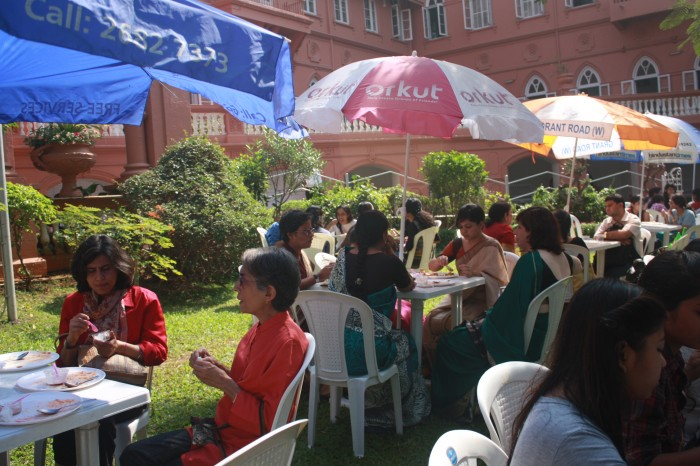 students and faculty gather around plastic tables set up on a lawn, eating and talking