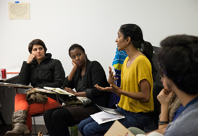 Facilitator Kavitha Rao gestures while speaking, several workshop attendees sit next to her, listening