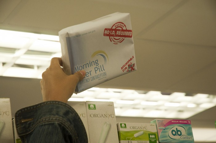 "Image of hand picking up box labeled ""Morning After Pill"" next to tampons on a shelf"