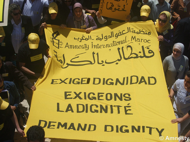 "Actvists carry a large yellow sign from Amnesty International Morocco that says ""Exige Dignidad / Exigeons La Dignite / Demand Dignity"""