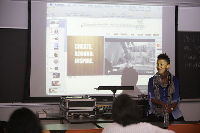 "Studio owner and entrepreneur Abhita Austin in front of her powerpoint, which displays the slide ""Create, Record, Inspire"""