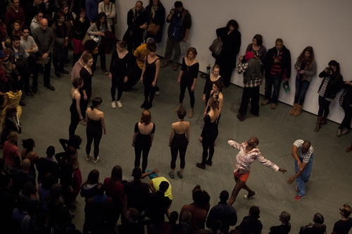 A circle of white dancers in black leotards, with several black dancers moving around them and the audience beyond that.