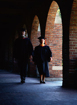 two professors in academic regalia walk on a university campus